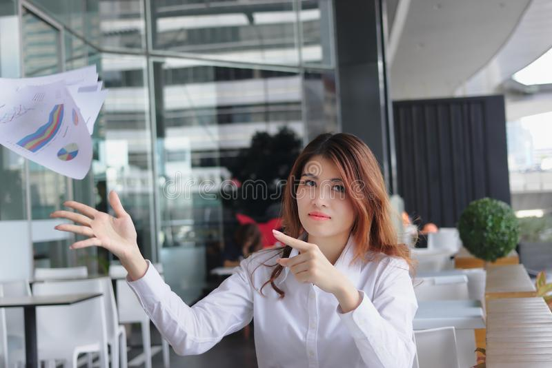 Stressed bored young Asian business woman throwing and pointing charts or paperwork at office royalty free stock photography