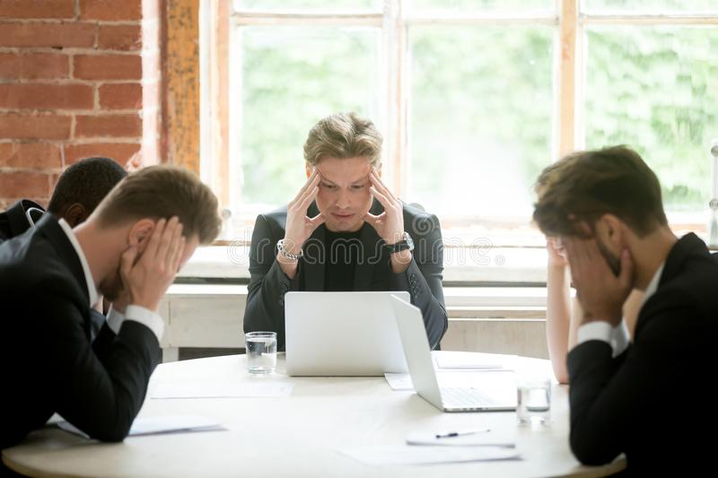 Stressed boss executive team searching business problem solution. Stressed boss and executive team searching problem solution at meeting, partners holding heads stock photo