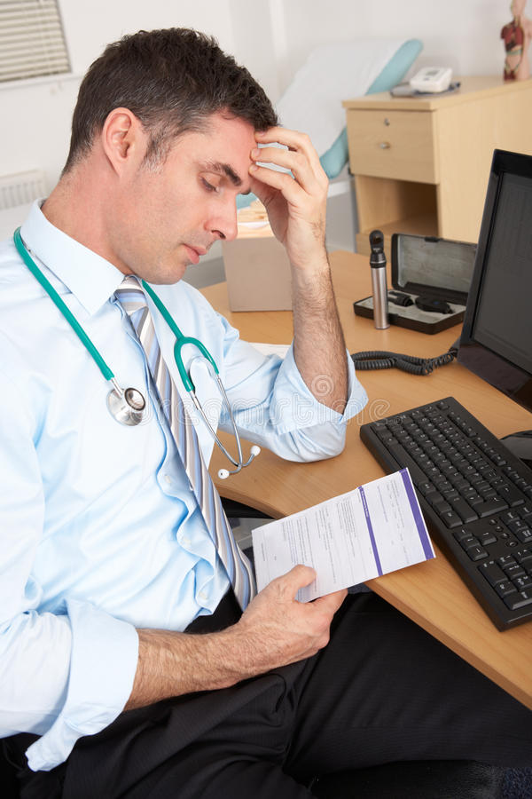 Download Stressed British GP Sitting At Desk Stock Image - Image of practitioner, doctors: 23958551