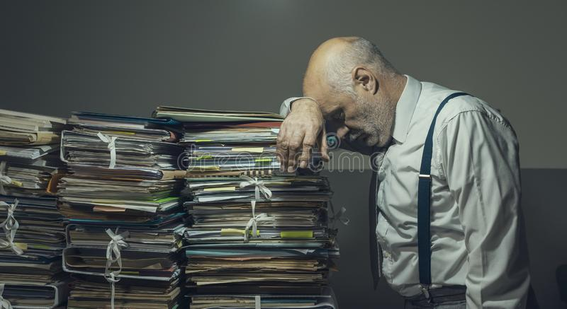 Stressed business executive overloaded with paperwork stock photo