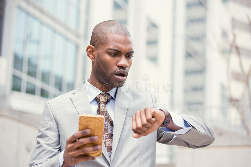 Stressed business man looking at wrist watch, running late for meeting outside corporate office. Business and time management concept. Stressed business man royalty free stock image