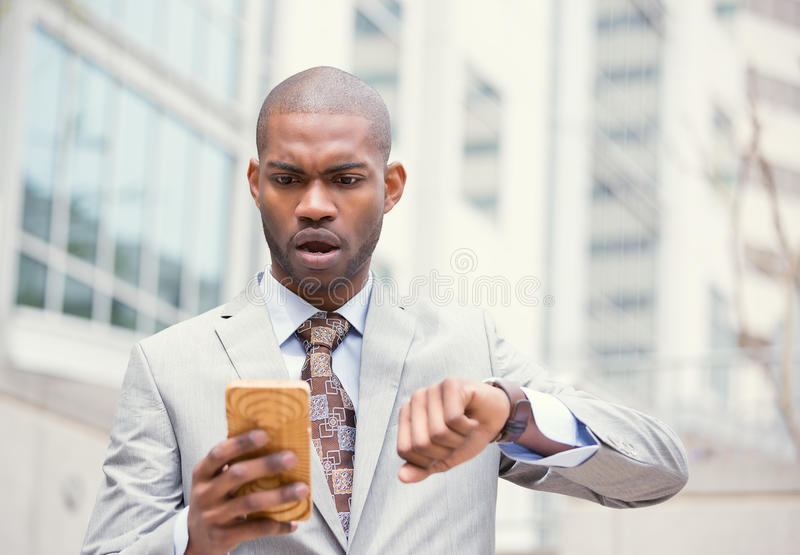 Stressed business man looking at wrist watch, running late for meeting outside corporate office. Business and time management concept. Stressed business man stock photos