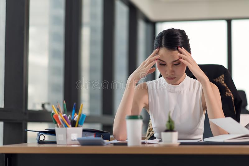 Stressed business woman with palm on face in her office royalty free stock image