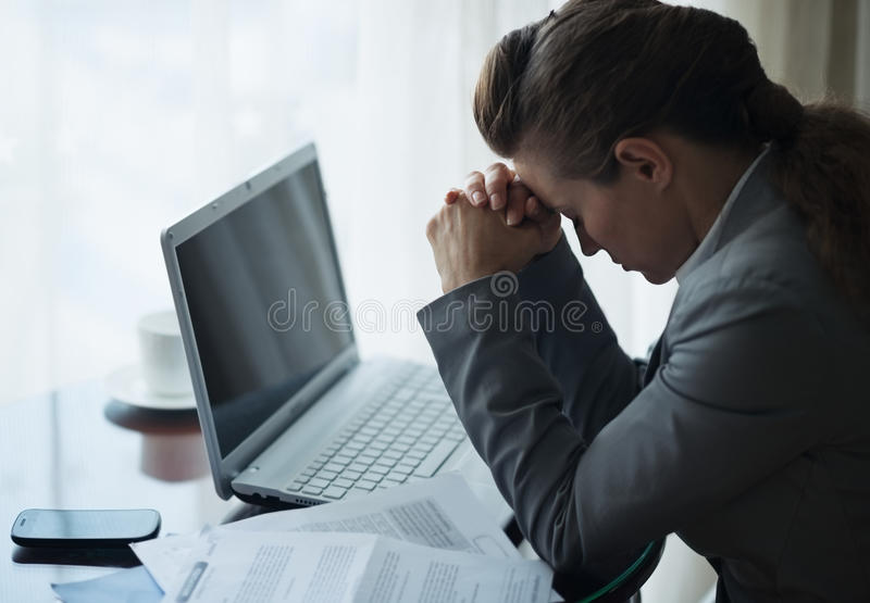 Stressed business woman working sitting at desk. In hotel room stock photography