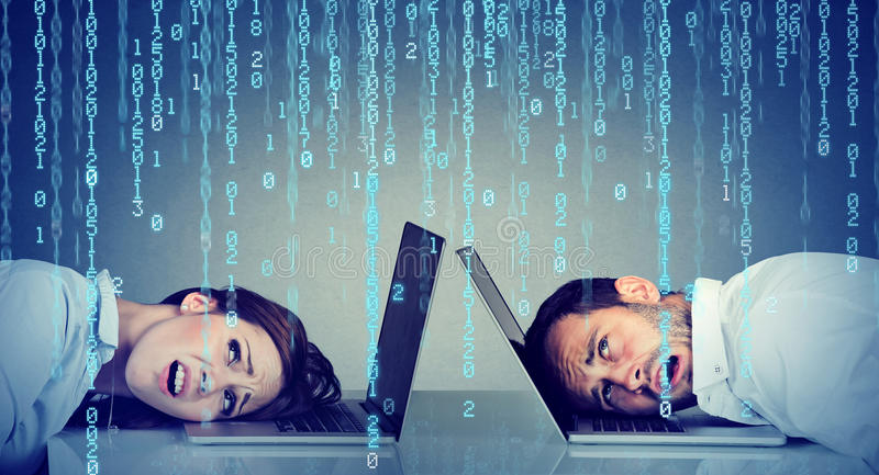 Stressed business woman and man resting head on laptop under binary code rain sitting at table. Stressed business women and men resting head on laptop under stock photos