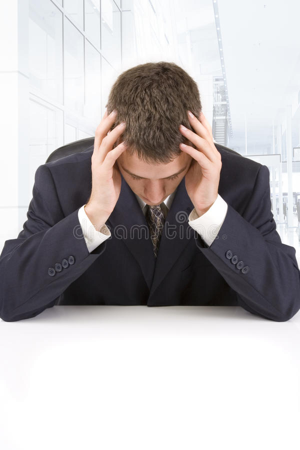 Stressed businessman. Sitting at his desk with head in hands royalty free stock photos
