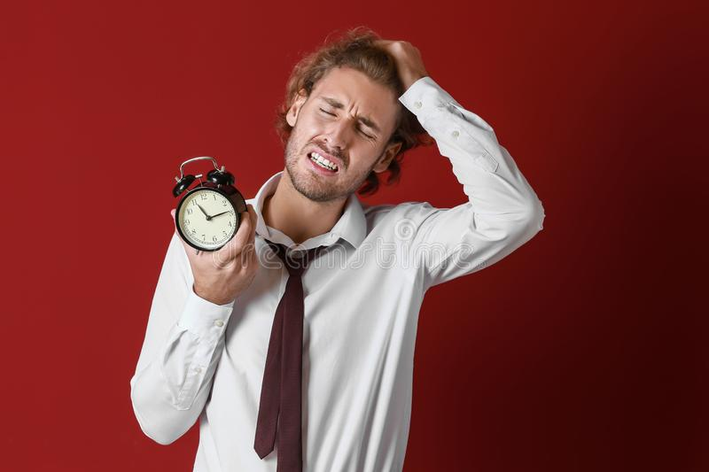 Stressed businessman with alarm clock on color background stock photography