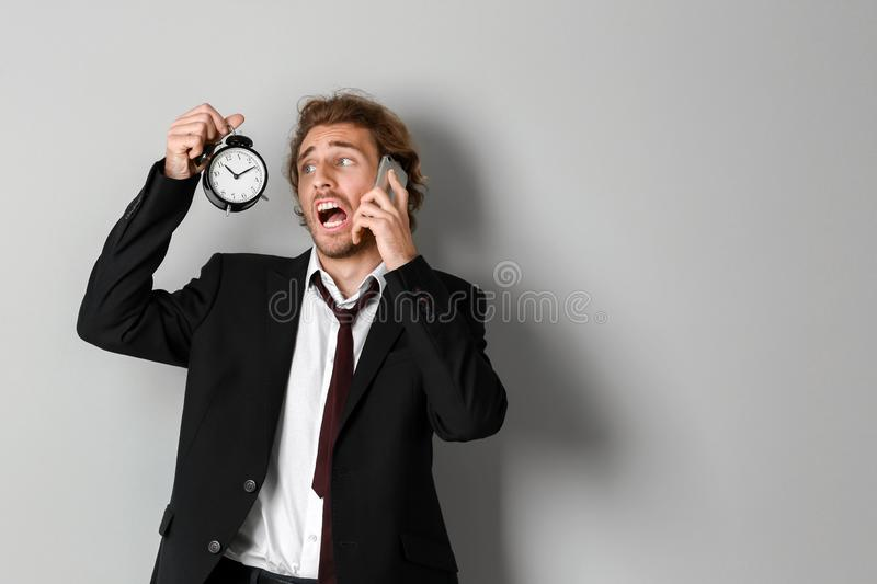 Stressed businessman with alarm clock talking by mobile phone on light background stock image