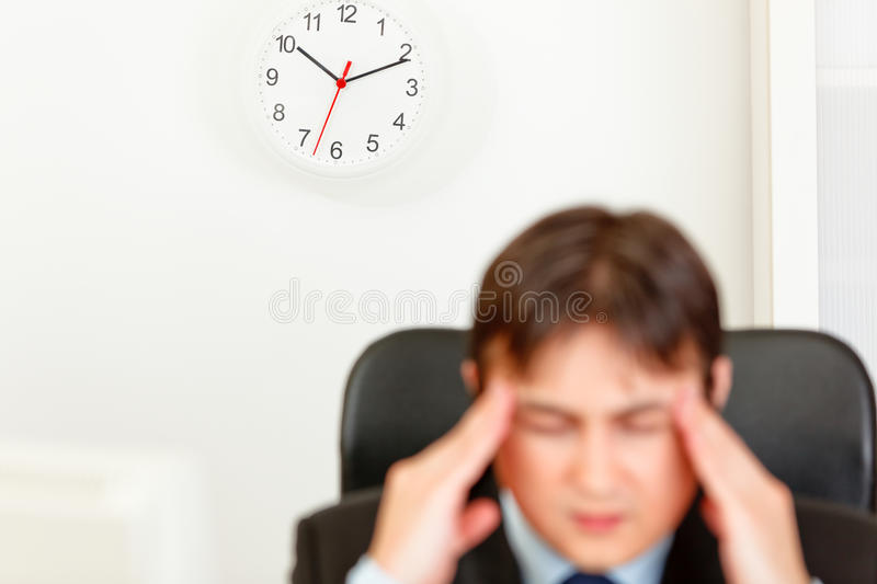 Stressed businessman aware of approaching deadline. Stressed business man aware of approaching deadline. Focus on clock royalty free stock photography