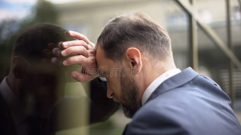 Stressed businessman banging head wall, work troubles pressure, disappointment. Stock photo royalty free stock photos