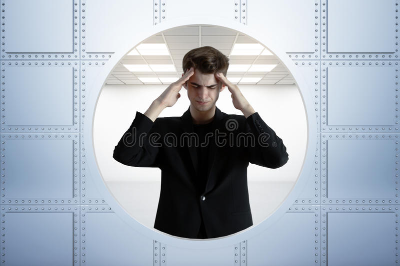 Stressed businessman in bank vault. Abstract image of stressed young businessman standing in bank vault. 3D Rendering royalty free stock image