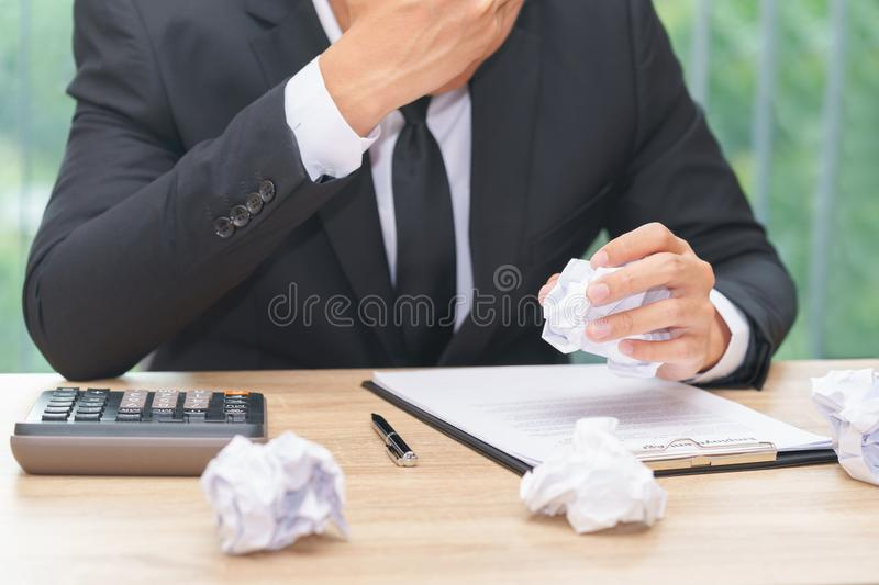 Stressed businessman crumple paper with calculator and contract. Document - making a mistake concept royalty free stock photo