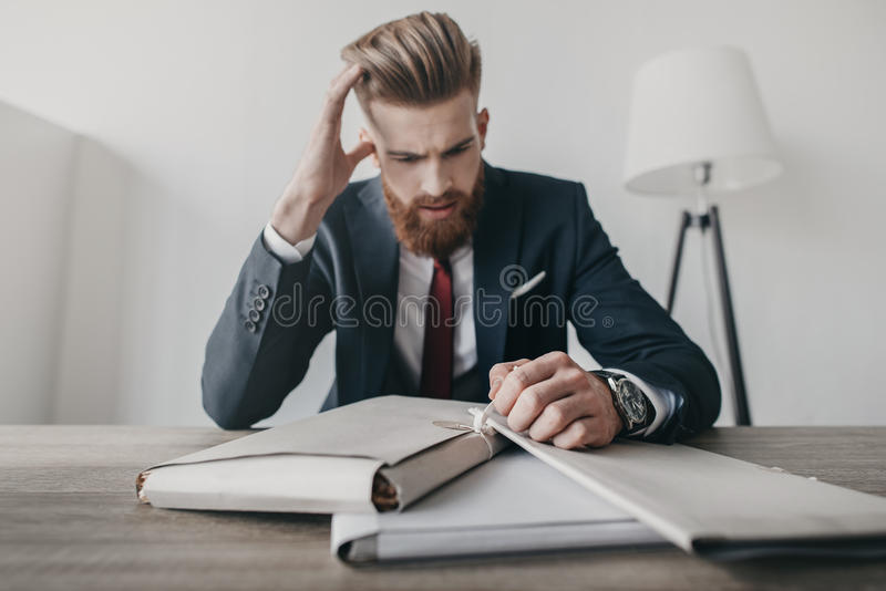 Stressed businessman with documents and folders sitting at table in office stock photo
