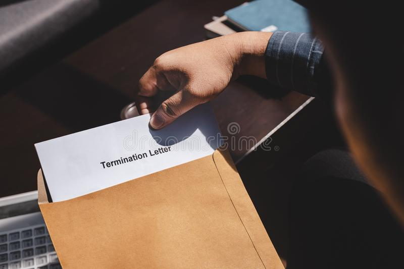 Stressed businessman feeling down after received Termination of Employment Form in paper brown envelope stock photo