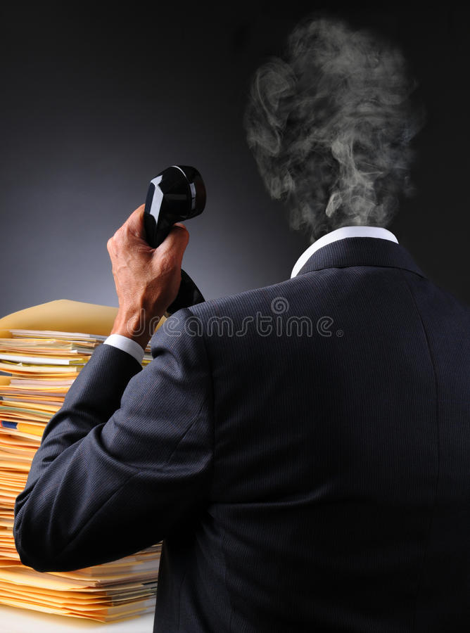 Stressed Businessman Head Explodes. A stressed businessman with files and telephone as his head explodes into a puff of smoke. Vertical format over a dark to stock photos