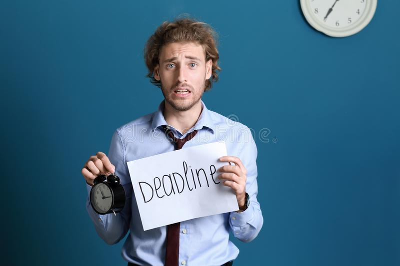 Stressed businessman holding sheet of paper with word DEADLINE and alarm clock on color background stock photography