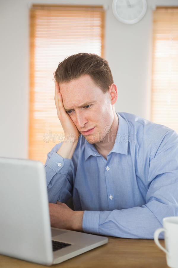 Stressed businessman looking at his laptop royalty free stock image