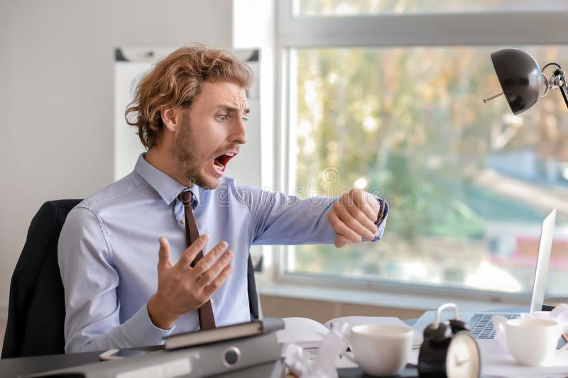 Stressed businessman missing deadlines in office royalty free stock images