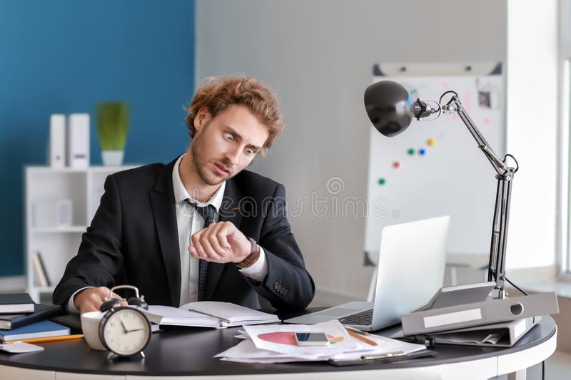 Stressed businessman missing deadlines in office royalty free stock photo