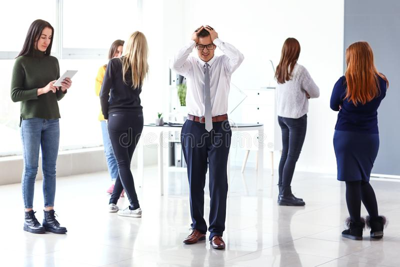 Stressed businessman in office with his colleagues stock photography
