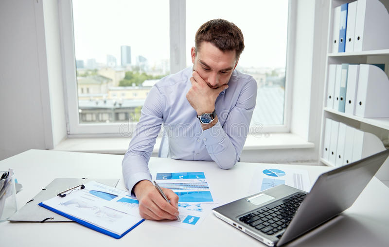 Stressed businessman with papers in office royalty free stock photos