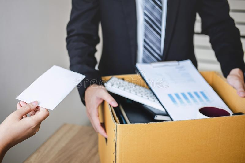 Stressed businessman receive fired letter from employer and packing belongings and files into brown cardboard box, changing and stock photos