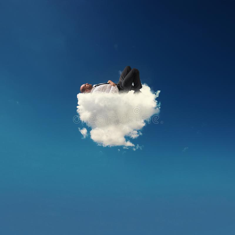 Stressed businessman relaxing on a soft cloud royalty free stock photo