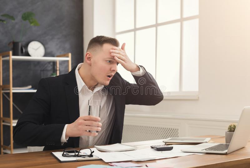 Stressed male manager working on laptop and drinking water royalty free stock photos