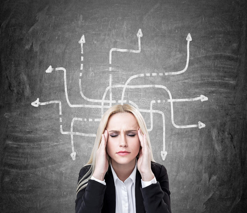 Stressed businesswoman. With arrows on dark concrete wall in the background royalty free stock images