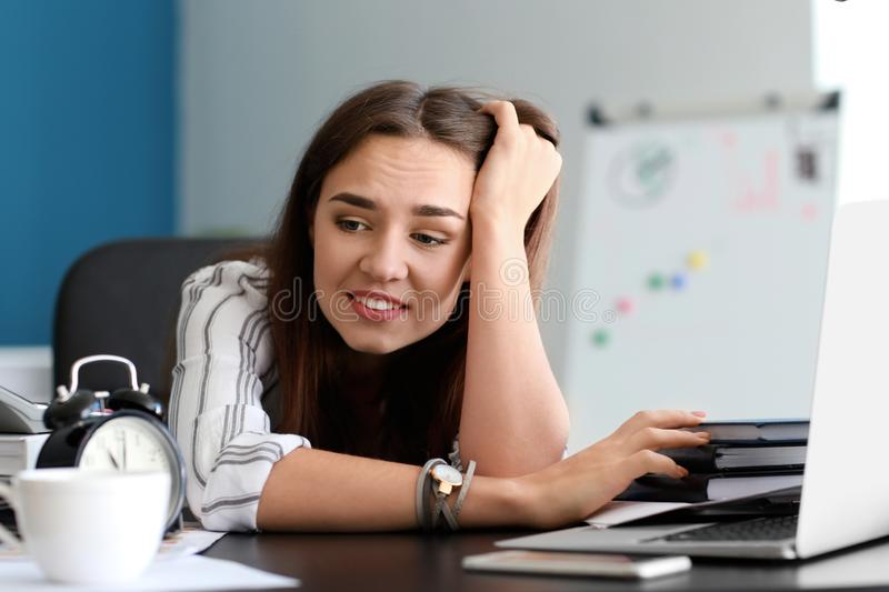 Stressed businesswoman missing deadlines in office stock photography