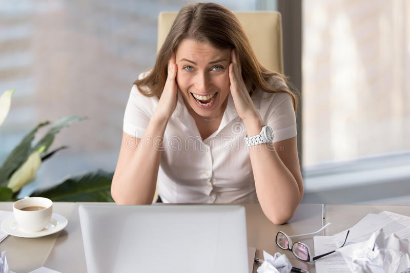 Stressed businesswoman screaming in hysterics, feeling desperate. Stressed businesswoman screaming in hysterics, holding head in hands, exhausted employee royalty free stock image