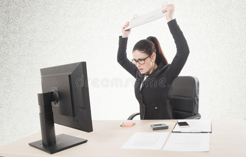 Stressed businesswoman sitting at table in front of computers. stock photography