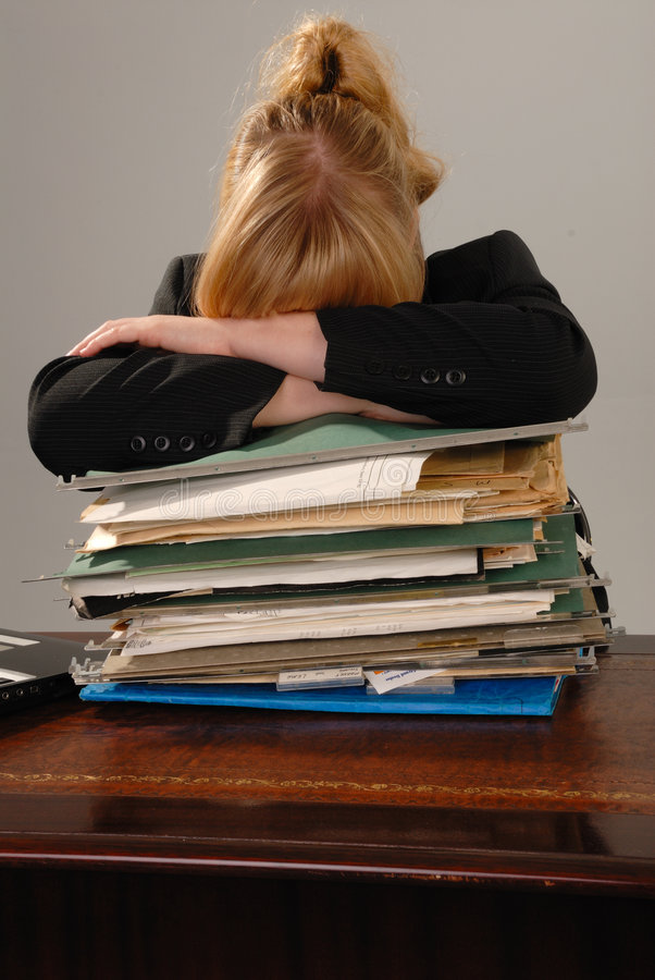Stressed businesswoman - stack of paperwork stock image