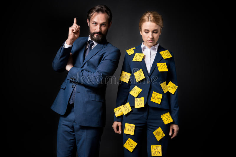 Stressed businesswoman with sticky notes on clothes standing near bearded businessman pointing up with finger stock photography
