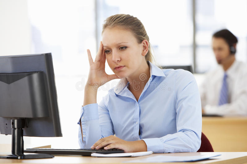 Stressed Businesswoman Working At Desk In Busy Office royalty free stock photography