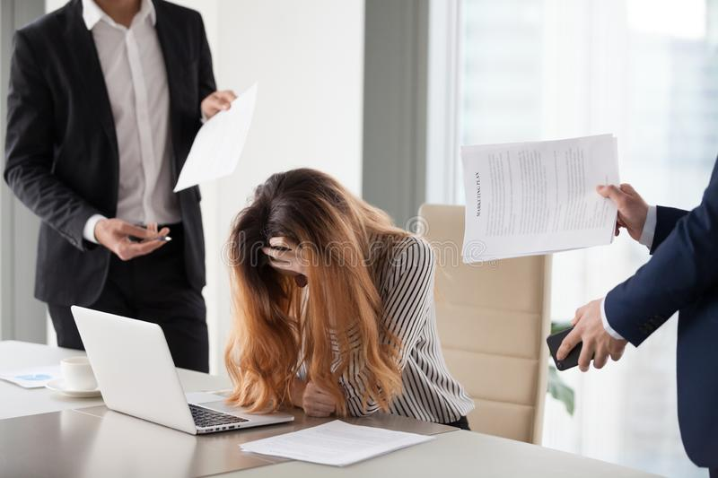 Stressed CEO annoyed by excessive workload and bothering colleag. Depressed businesswoman feeling stressed bothered by male colleagues at work, female CEO suffer stock photos