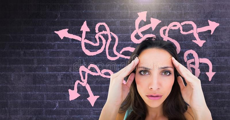 Stressed confused woman with pink arrow squiggly doodles on wall. Digital composite of Stressed confused woman with pink arrow squiggly doodles on wall royalty free stock photography