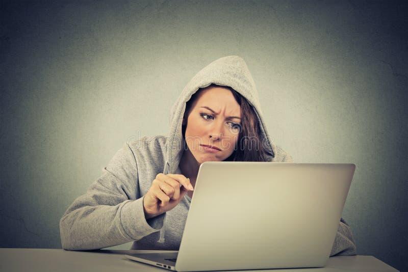 Stressed a contrarié la femme inquiétée s'asseyant devant l'ordinateur portable images stock