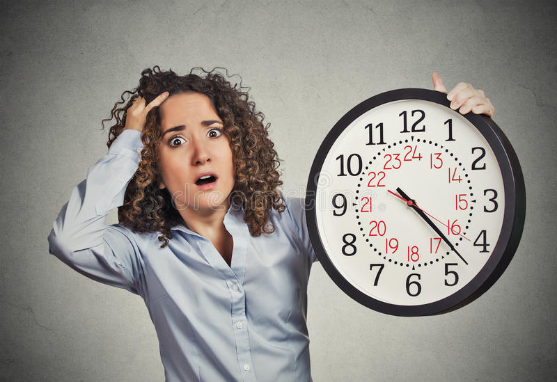 Stressed corporate employee holding clock looking anxiously running out of time. Time pressure. Closeup portrait woman stressed corporate employee holding clock stock photo