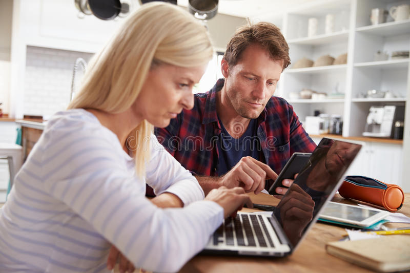 Stressed couple sitting in their kitchen using computers stock photos