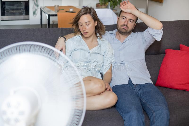 Tropical climate and air conditioner is needed. Stressed couple trying to refresh from summer heatwave royalty free stock photography