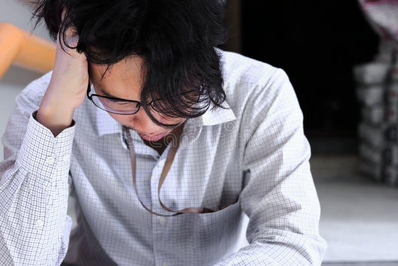 Stressed deprimerad ung asiatisk affärsman som lider från sträng fördjupning royaltyfri bild