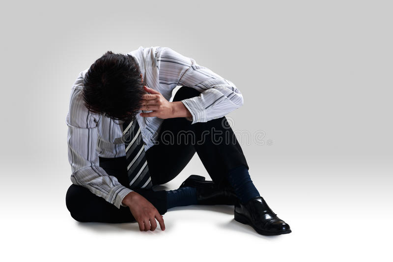 Stressed disappointed businessman sitting alone. On floor, Isolated on grey background royalty free stock photo