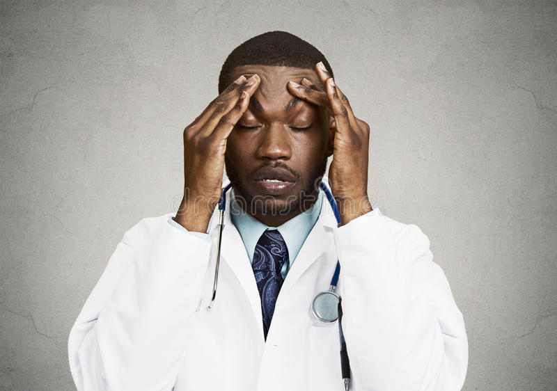 Stressed doctor, health care professional. Closeup portrait sad health care professional with headache, stressed, holding head with hands. Nurse, doctor with royalty free stock images