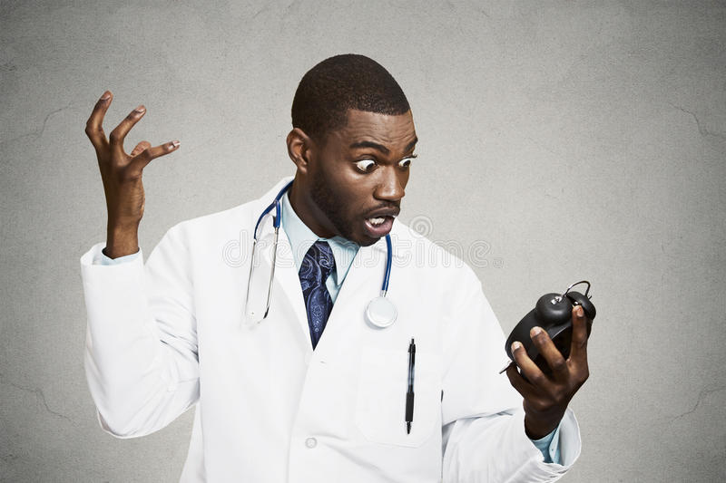 Stressed doctor, holding alarm clock stock photography