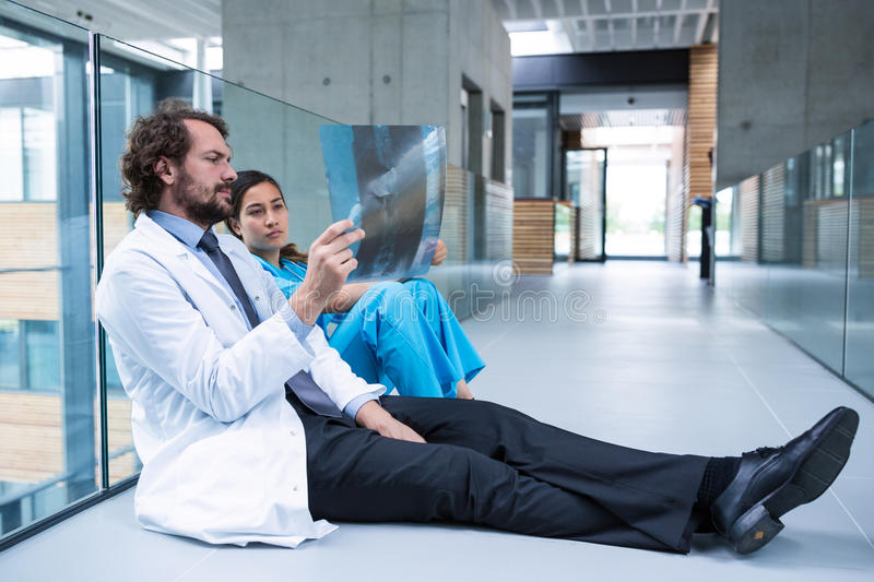 Stressed doctor and nurse sitting on floor examining X-ray report. Stressed doctor and nurse examining X-ray report in hospital corridor royalty free stock image