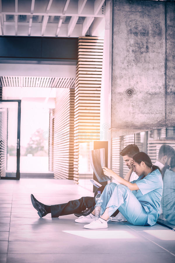 Stressed doctor and nurse sitting on floor examining X-ray report. Stressed doctor and nurse examining X-ray report in hospital corridor royalty free stock images