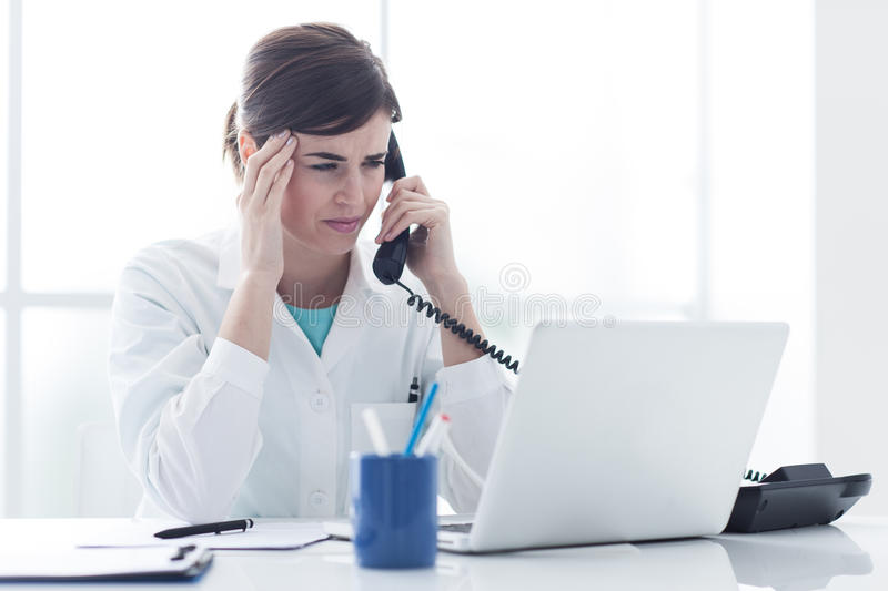 Stressed doctor on the phone. Stressed female doctor working at office desk and answering phone calls, she is having an headache and touching her temple royalty free stock photography