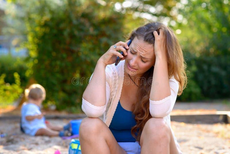 Stressed drückte die Mutter nieder, die auf einem Mobile spricht stockfotos