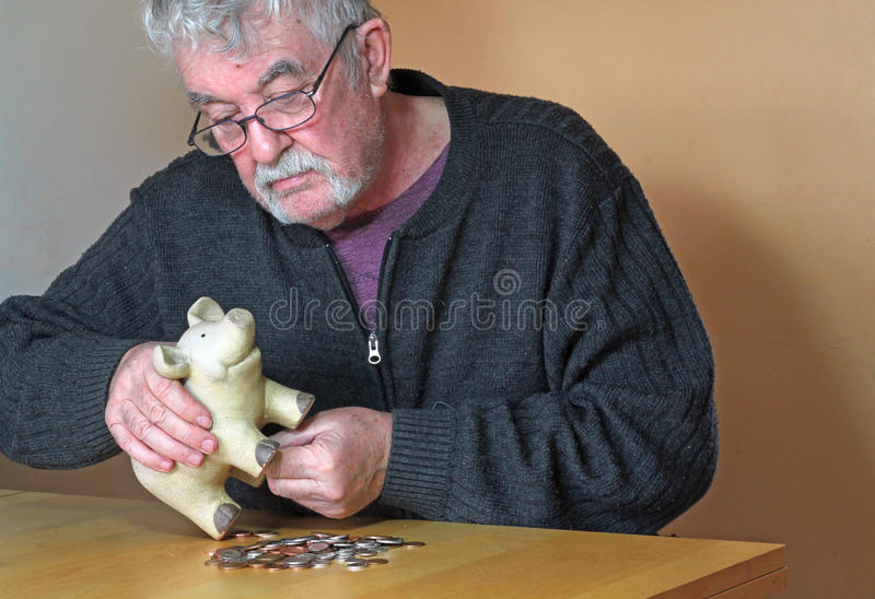 Stressed elderly man emptying piggy bank. stock photo
